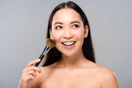 Photo pour Femme asiatique nue de sourire avec le pinceau cosmétique d'isolement sur le gris - image libre de droit