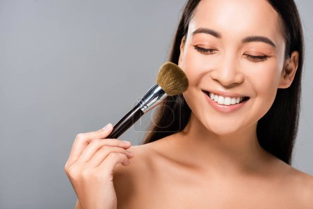 Photo pour Femme asiatique nue heureuse avec le pinceau cosmétique d'isolement sur le gris - image libre de droit