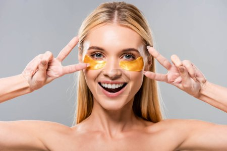 Photo pour Happy naked blonde young woman with eye patches showing peace signs isolated on grey - image libre de droit