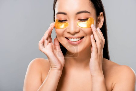 Photo for Smiling naked asian woman with eye patches on face isolated on grey - Royalty Free Image
