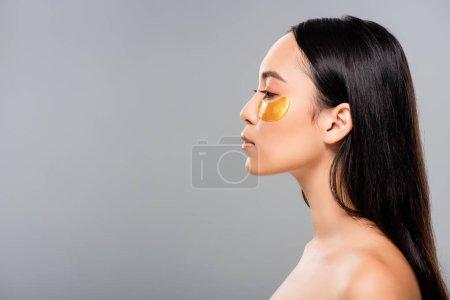 Photo pour Vue latérale de la femme asiatique nue avec des corrections d'oeil sur le visage isolé sur le gris - image libre de droit