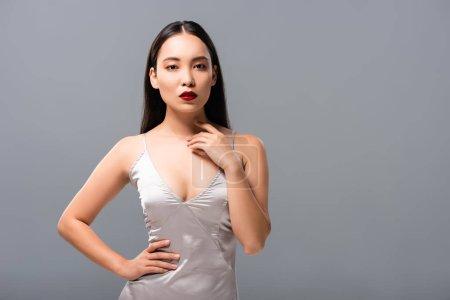 Photo pour Femme asiatique attirante dans la robe de satin avec les lèvres rouges posant d'isolement sur le gris - image libre de droit