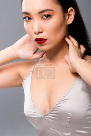Photo pour Femme asiatique dans la robe de satin avec les lèvres rouges d'isolement sur le gris - image libre de droit