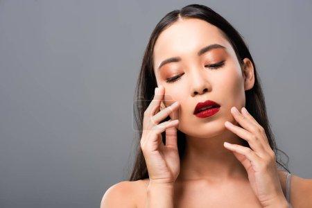 Photo pour Belle femme asiatique avec des lèvres rouges touchant le visage isolé sur le gris - image libre de droit
