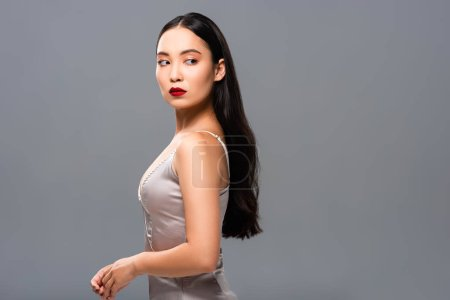 Photo for Side view of beautiful smiling asian woman in satin dress with red lips isolated on grey - Royalty Free Image