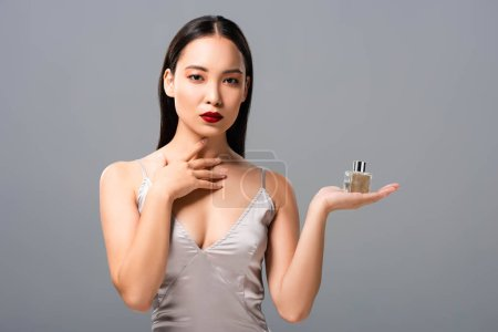 Photo for Elegant asian woman in elegant dress with red lips holding perfume isolated on grey - Royalty Free Image