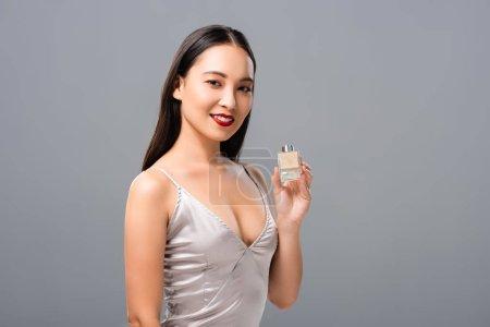 Photo pour Femme asiatique de sourire dans la robe élégante avec les lèvres rouges retenant le parfum d'isolement sur le gris - image libre de droit