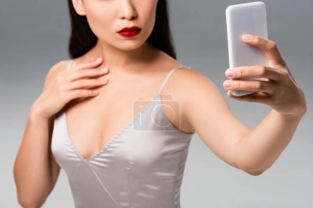 Photo for Cropped view of beautiful woman in satin dress with red lips taking selfie isolated on grey - Royalty Free Image