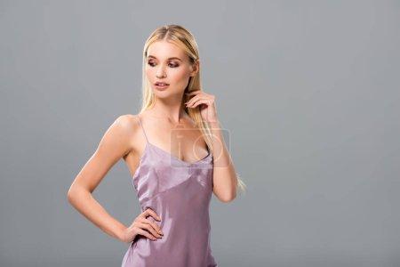 Photo pour Fille blonde élégante dans la robe de satin violet regardant vers le bas avec la main sur la hanche d'isolement sur le gris - image libre de droit