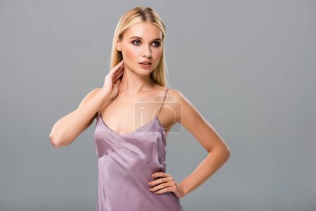 Photo for Elegant blonde girl in violet satin dress posing isolated on grey - Royalty Free Image