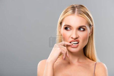 Photo pour Blonde fille montrant dents et regardant loin isolé sur gris - image libre de droit