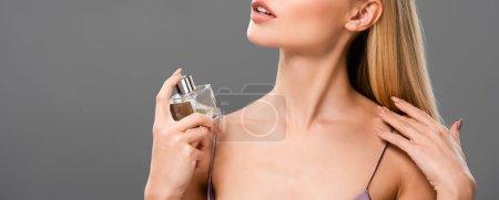 Photo pour Vue recadrée de femme blonde élégante dans le parfum violet de robe de satin pulvérisant avec les yeux fermés isolés sur le gris - image libre de droit