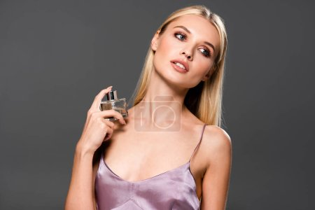 elegant blonde woman with perfume looking away  isolated on grey