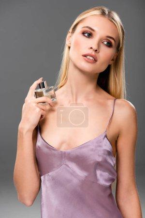 Photo pour Femme blonde élégante dans la robe violette de satin avec le parfum regardant loin isolé sur le gris - image libre de droit