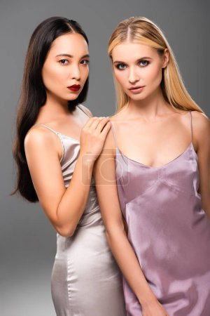 Photo for Elegant european blonde and asian brunette women in satin dresses isolated on grey - Royalty Free Image