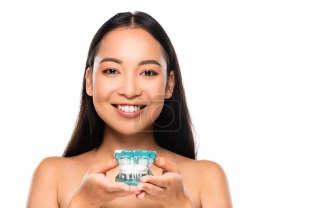 Photo for Smiling naked asian woman holding jaw model isolated on white - Royalty Free Image