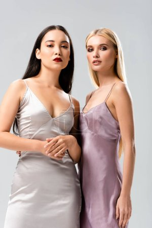 Photo for Low angle view of elegant blonde and brunette women in satin dresses isolated on grey - Royalty Free Image
