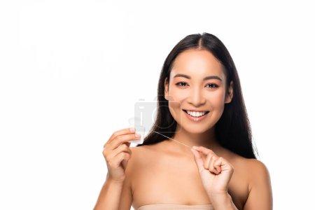 lächelnde asiatische Frau mit Zahnseide isoliert auf weiß