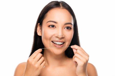 Photo pour Femme nue asiatique de sourire retenant la soie dentaire d'isolement sur le blanc - image libre de droit