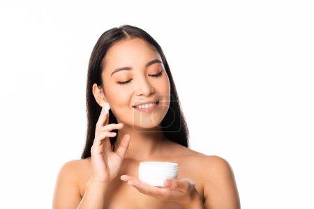 Photo pour Belle femme asiatique nue de sourire appliquant la crème cosmétique d'isolement sur le blanc - image libre de droit