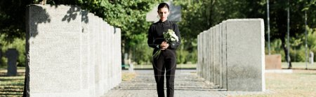 Photo for Panoramic shot of upset woman holding flowers and walking in graveyard - Royalty Free Image