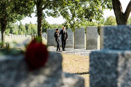 Photo for Selective focus of man and woman walking near tombstones in cemetery - Royalty Free Image