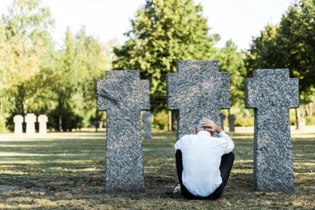 Photo for Back view of man with grey hair sitting near gravestones in cemetery - Royalty Free Image