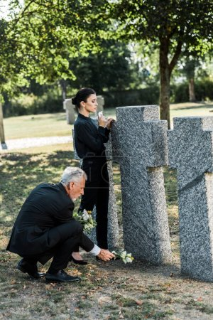 Photo for Senior man putting flowers near tombs and woman in cemetery - Royalty Free Image
