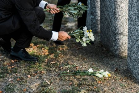 Photo for Cropped view of senior man putting flowers near tombs - Royalty Free Image