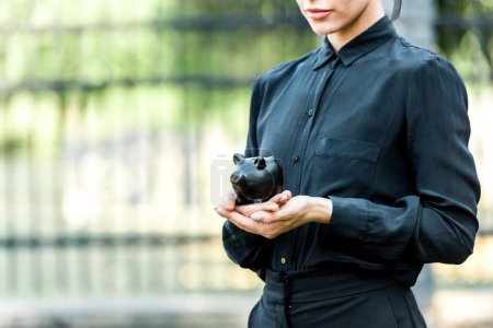 cropped view of woman holding black piggy bank