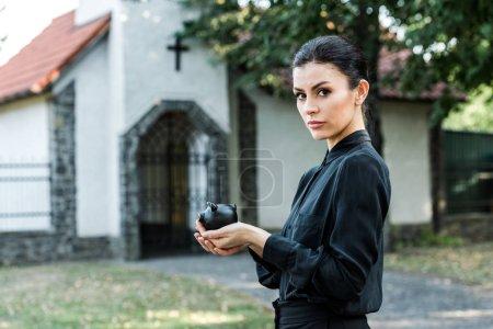 Photo pour Femme attirante retenant la tirelire noire près de l'église - image libre de droit
