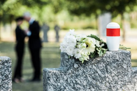 Photo pour Selective focus of bouquet of white flowers and cemetery urn on tombstone - image libre de droit