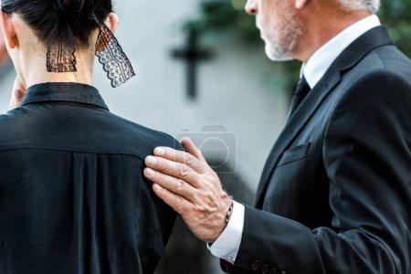 Photo pour Vue recadrée de l'homme touchant la femme sur l'enterrement - image libre de droit