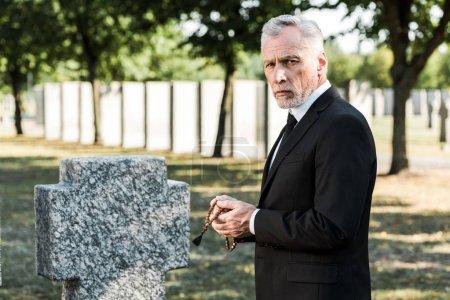 Photo pour Homme avec le cheveu gris retenant des perles de chapelet près de la pierre tombale - image libre de droit