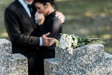 Photo pour Foyer sélectif de bouquet sur la pierre tombale près de l'homme étreignant femme - image libre de droit