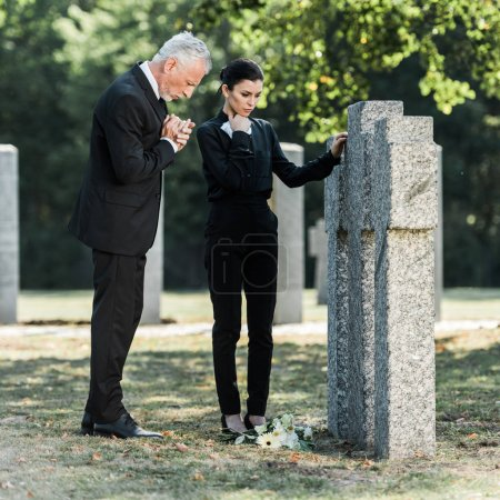 Photo for Upset man with grey hair and attractive woman standing near tombs - Royalty Free Image