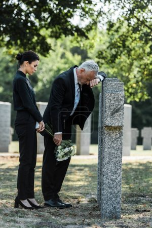 Photo for Attractive woman holding flowers near tombstones and upset senior man - Royalty Free Image