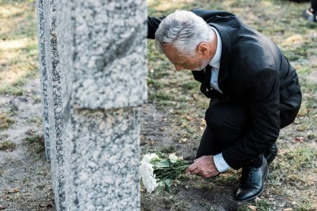 Photo for Selective focus of senior man putting white flowers near tomb - Royalty Free Image