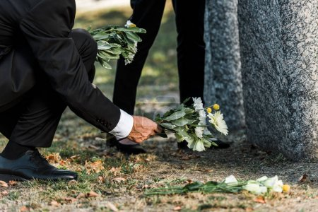Photo for Cropped view of senior man putting flowers near tombstones and woman - Royalty Free Image