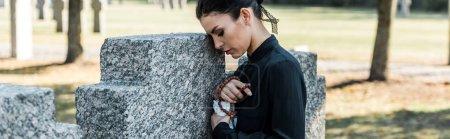 Photo pour Tir panoramique de la femme triste retenant des perles de chapelet près des tombes - image libre de droit