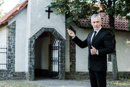 Photo pour Homme aîné affichant le pouce vers le haut et pointant avec le doigt à l'église - image libre de droit