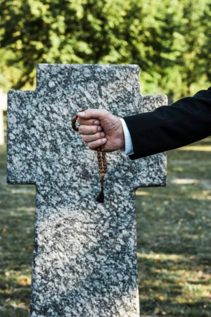 Photo pour Cropped view of senior man holding rosary beads near tombstone - image libre de droit