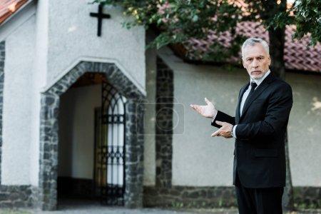 Photo pour Bel homme aîné en costume gesticulant près de l'église - image libre de droit