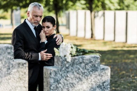 Photo for Selective focus of man hugging woman while looking at flowers on tomb - Royalty Free Image