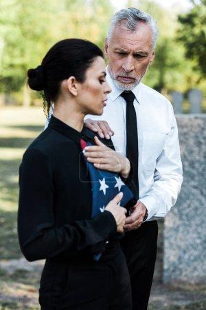 Photo pour Foyer sélectif de l'homme barbu regardant la femme avec le drapeau américain sur l'enterrement - image libre de droit