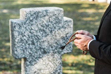 Photo for Cropped view of man holding rosary beads near tombstone - Royalty Free Image