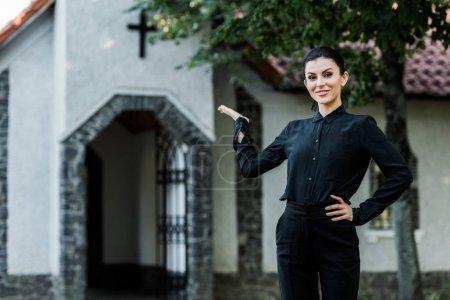 Photo pour Femme gai restant avec la main sur la hanche tout en faisant des gestes près de l'église - image libre de droit