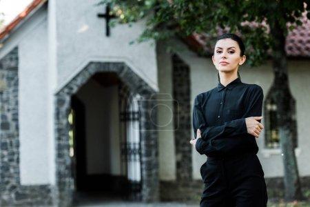 Photo pour Femme attirantrestant avec les bras croisés près de l'église - image libre de droit