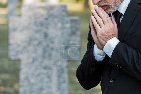 Photo for Cropped view of senior man standing with praying hands - Royalty Free Image