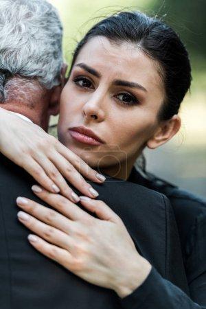 Photo pour Bouleversé femme étreignant homme âgé et regardant caméra - image libre de droit